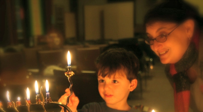 A child and an adult watching the Hanukkah lights