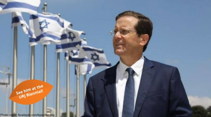 Isaac Herzog standing in front of a row of Israeli flags against a blue sky