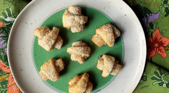 Plate of pineapple rugelach on a floral tablecloth