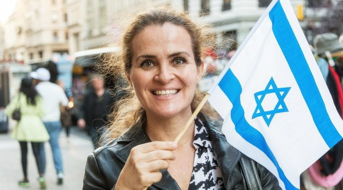 Smiling woman standing outside and waving a small Israeli flag