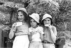 Girls with hats eating matzah at a youth village in Israel (1960s)