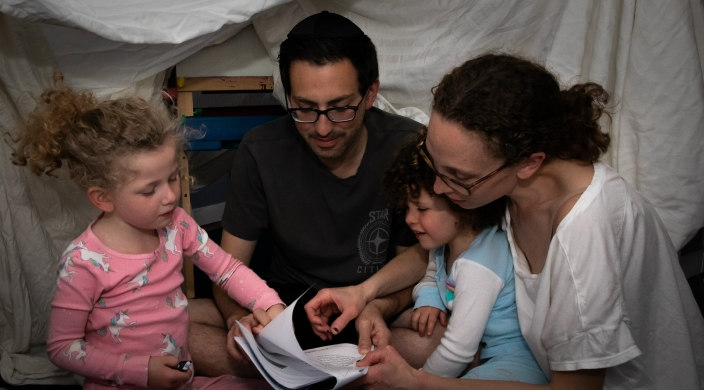 The author with her husband and two children reading a book in the fort they created