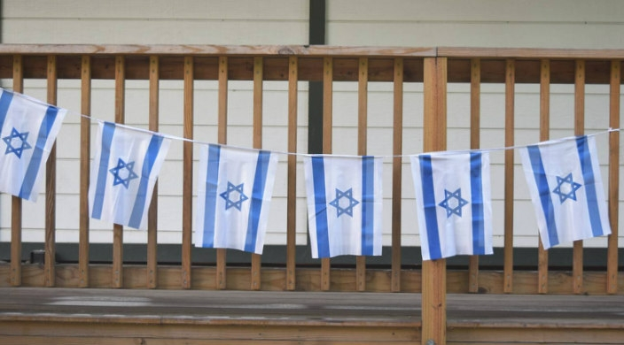 Israeli flags hanging from a wooden porch railing