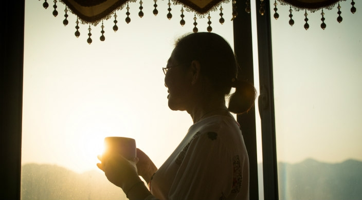 Woman holding a mug and looking out a large window during sunrise