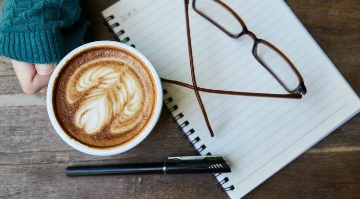 Womans hand holding a coffee cup next to a pen and a pad of paper
