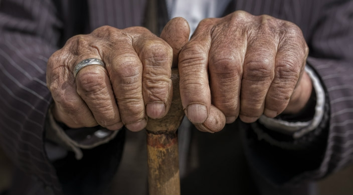 Close up of the hands of an elderly man clutching the top of a cane
