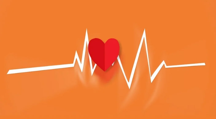 Red paper heart against an orange background with a white line through it like an echo cardiogram