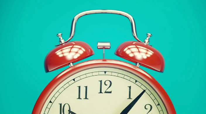 top of a red alarm clock against a blue background