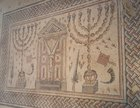 "Jewish synagogue mosaic emphasizing the symbology of the Temple. Two menorahs flank a curtained ""ark"" in the center (likely the cupboard for Torah scrolls), around which float rams' horns, incense shovels, palm fronds and citron. 4th century CE, Hamat Tiberias, Israel."