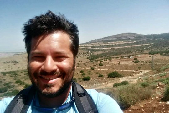 Matt Adler smiles at the camera while wearing backpack and taking a selfie in front of an Israeli desert setting