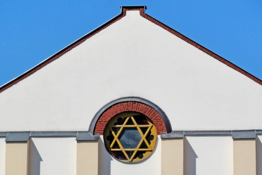 Outside of a white synagogue building with a Star of David stained glass window