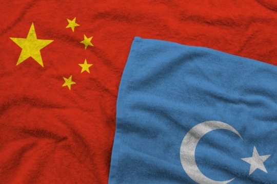 Red Chinese flag and blue Uyghur flag lying atop one another