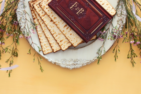 White platter with a stack of matzah and an old Haggadah on top all against a yellow table