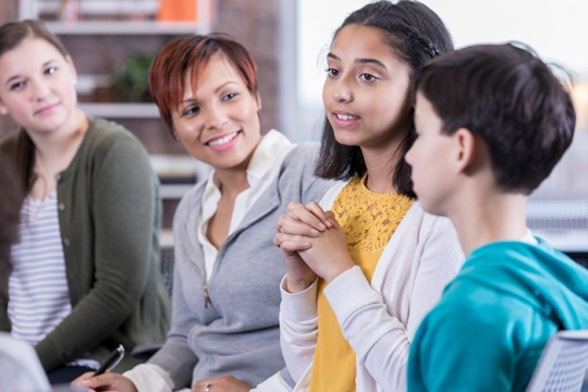 Students in a discussion with adults