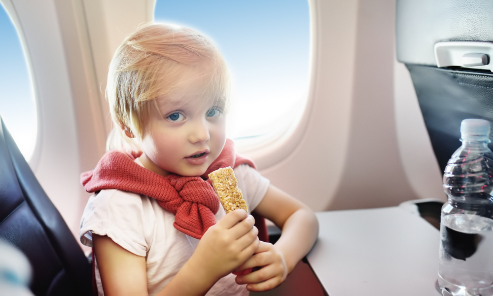 what to pack in your carry-on: Little boy drinking water and eating snack during the flight.