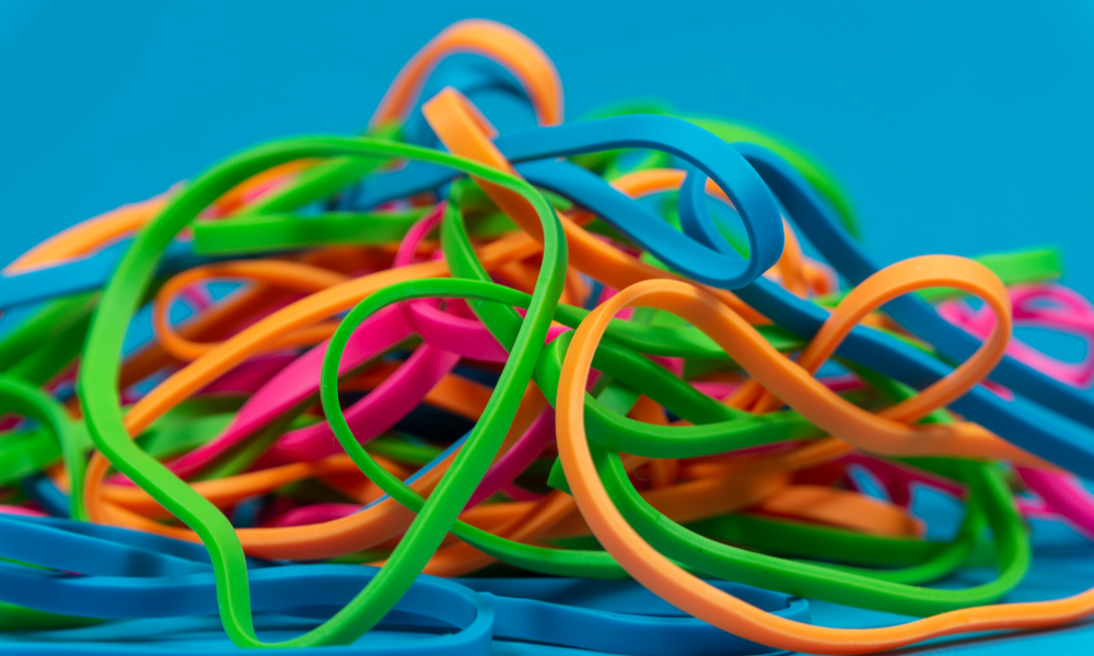 what to pack in your carry-on: Pile of colorful rubber bands over blue background