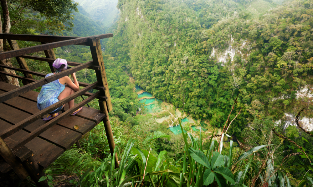fun places to go visit in 2020: Photographer on the lookout point on the Cascades National Park in Guatemala Semuc Champey
