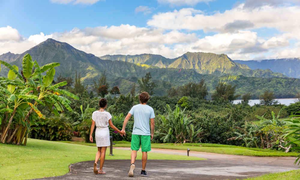 The Best Winter Getaways Where You Can Forget the Cold: Couple tourists walking on Hawaii vacation.