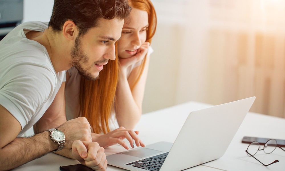 Everything You Need to Know About Open Jaw Flights: young Couple Using Laptop On Desk At Home