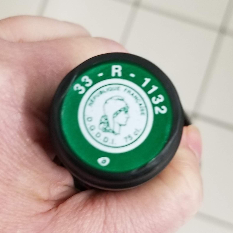 "Tax stamp on French wine saying ""R"" for récontant. The green color indicates that it is an AOC wine, which had to be taste-tested before being sold."