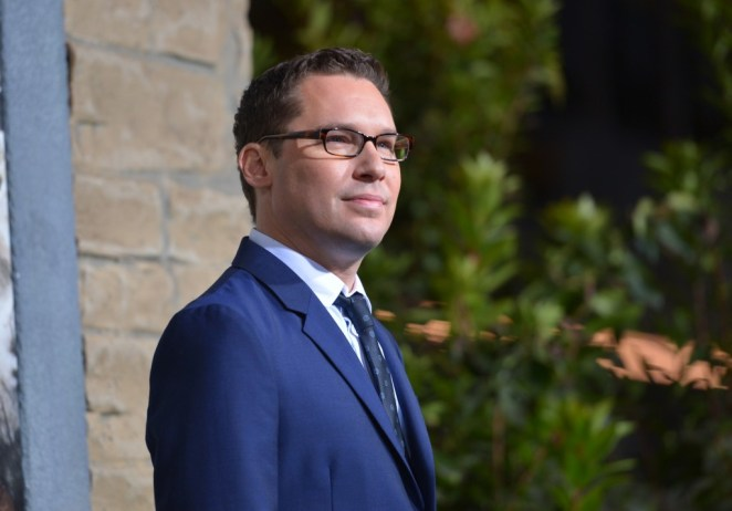 Bryan Singer, wearing a blue suit and glasses, looking to the right of the frame