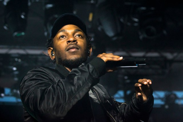 Kendrick Lamar holds a microphone on stage