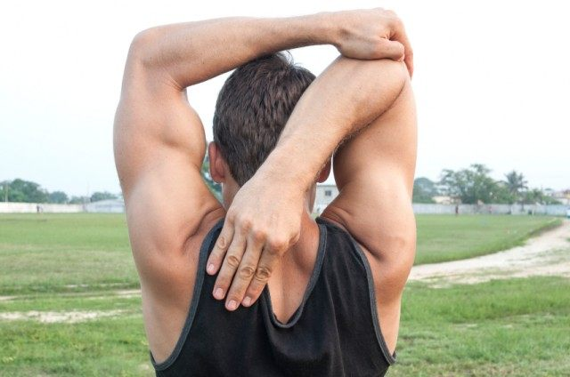 Man performing triceps stretch outside