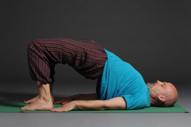 male yoga practitioner in bridge pose