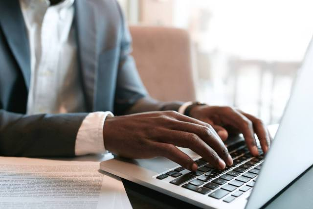 Businessman working on laptop with some documents on table