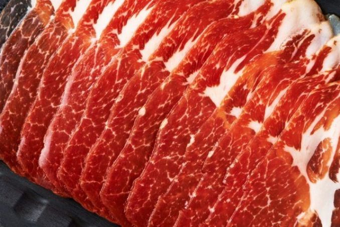 Red slices of meat in a black background.