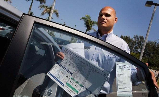 A car salesman prepares a car for a new customer