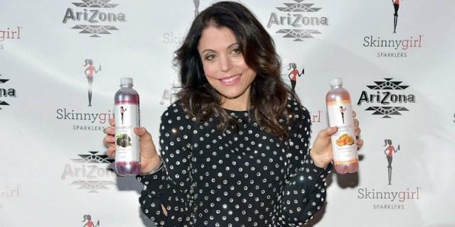 Bethenny Frankel holds up two bottles of Arizona Beverages SkinnyGirl Sparklers and smiles