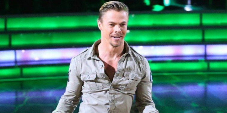 Derek Hough in a khaki shirt dancing on Dancing with the Stars