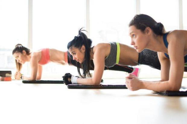 Three women doing plank exercise lying on yoga mat in fitness class.