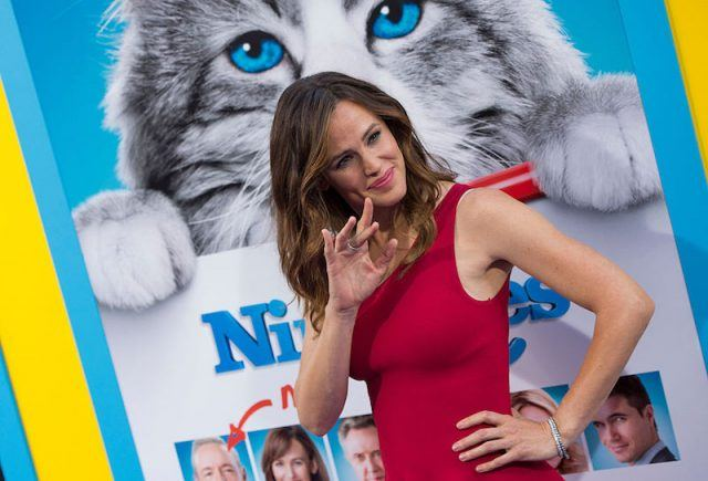 Jennifer Garner waves at the paparazzi in a red dress at her movie premiere.