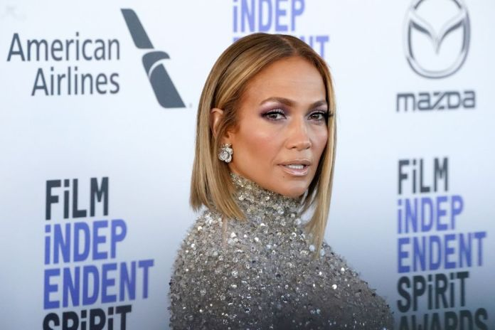 Jennifer Lopez smiling in front of a repetitive background