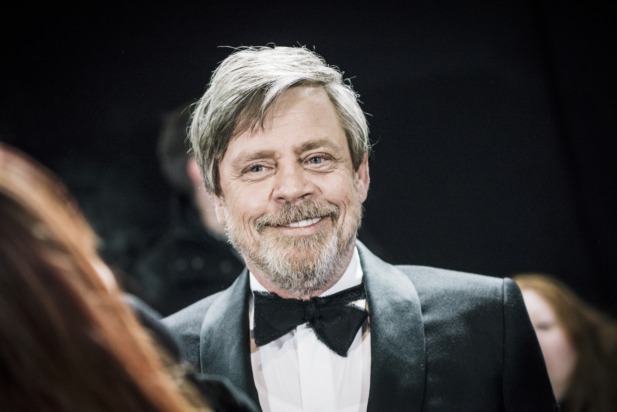 Mark Hamill smiling, with suit and bowtie