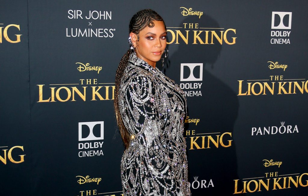 Beyoncé a little smiling, looking back, in front of a black background with the 'Lion King' logo