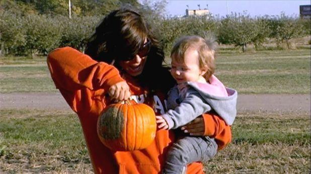 Chelsea Hauska and daughter Rey Bray smiling at a pumpkin