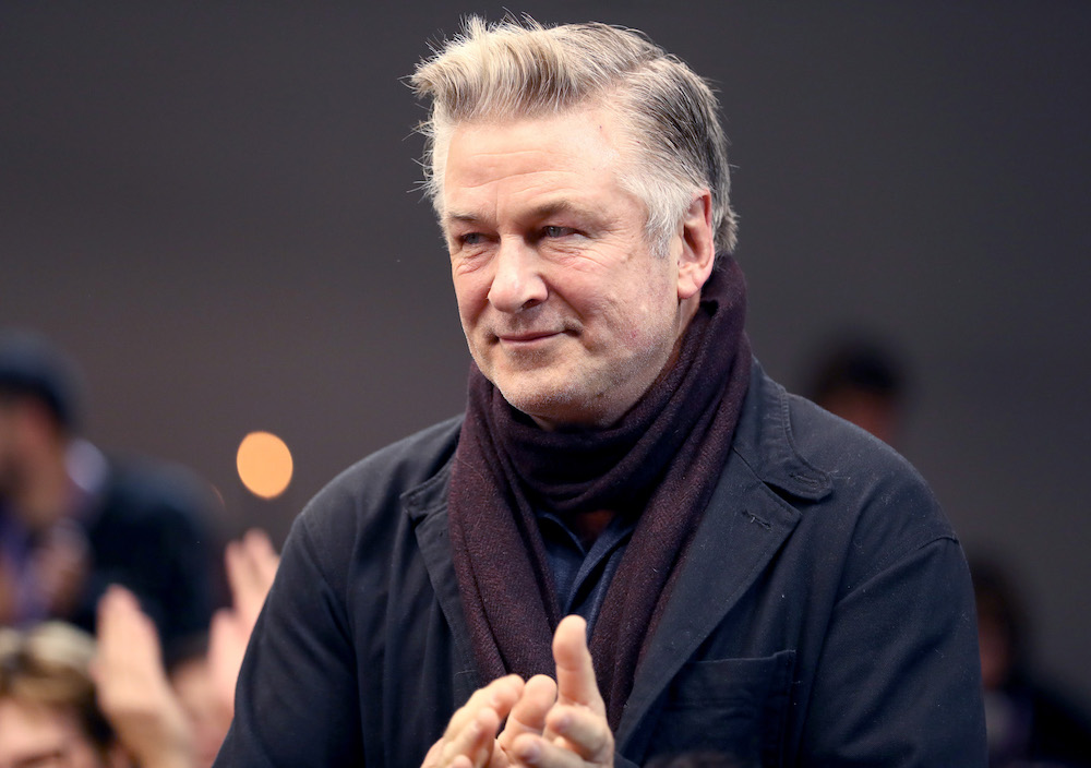 Alec Baldwin looking to the left in front of a dim background