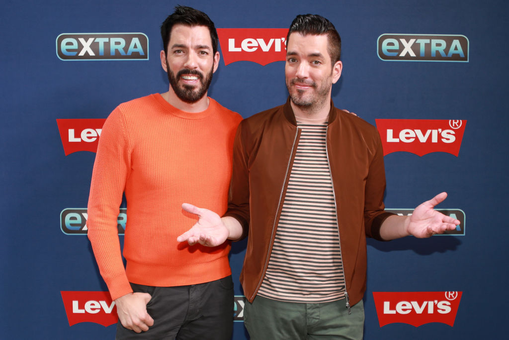 (LR) Drew Scott and Jonathan Scott smiling in front of a blue background