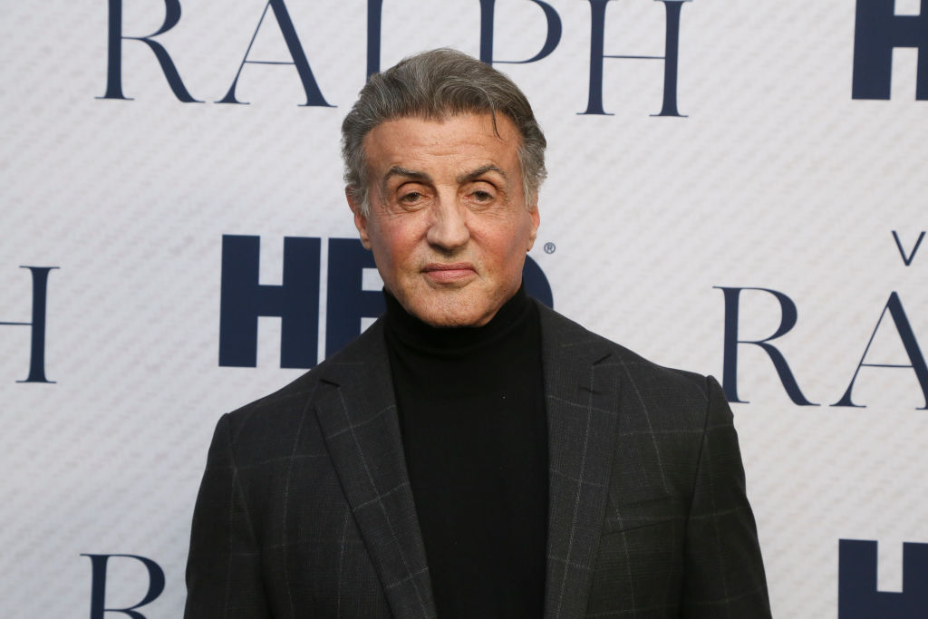 Sylvester Stallone smiles a little in front of a white background with repetitive text