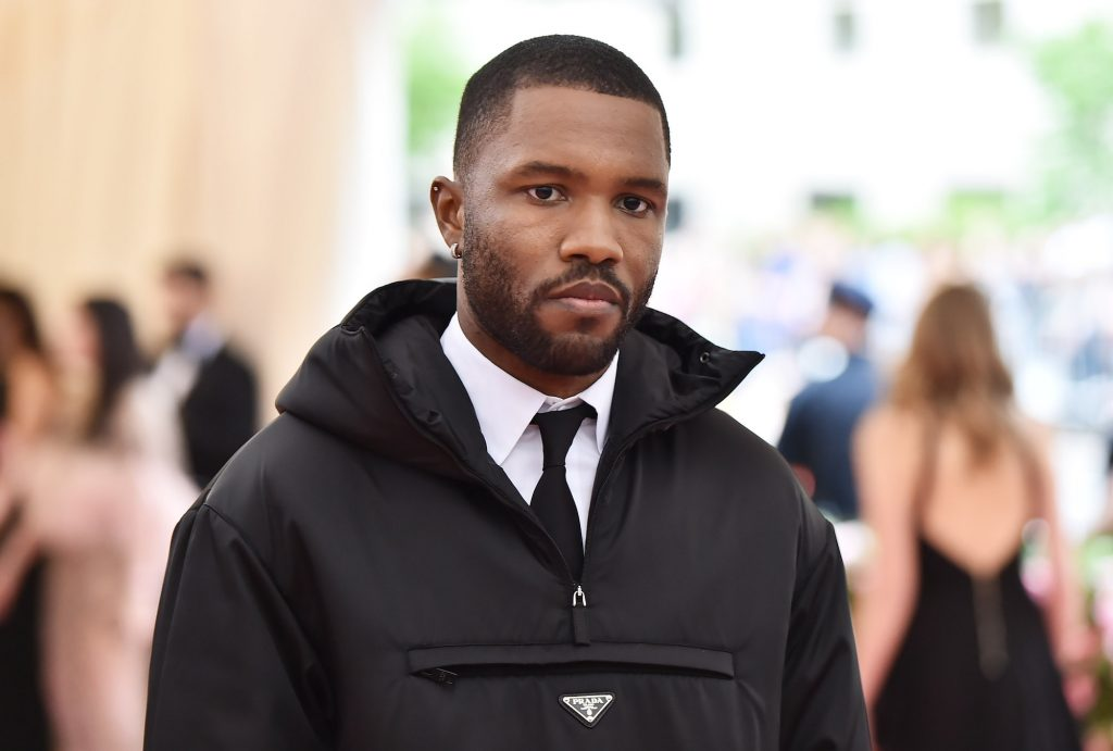 Frank Ocean looks down in front of an obscure crowd