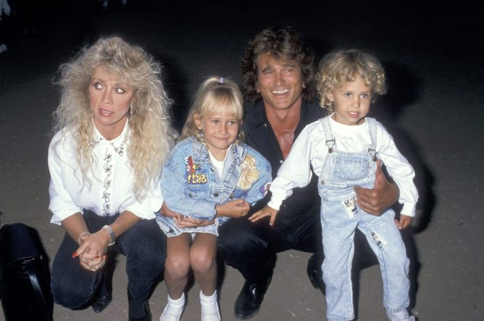 Cindy Landon in a white shirt and black jeans, Jennifer Landon in a denim jacket and white tennis shoes, Michael Landon in a black shirt and black pants, Sean Landon in a denim overall dress and a white shirt.