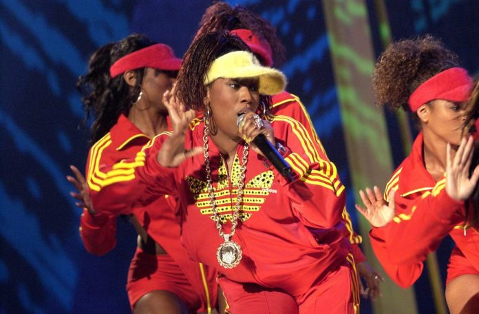 Missy Elliot is wearing a red and yellow track suit with a yellow hat.