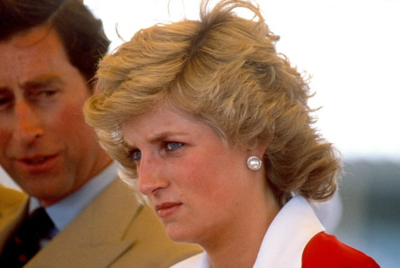 Princess Diana pictured from just below her neck up standing near Prince Charles in a red dress with a white collar