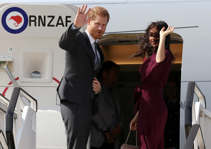 Prince Harry and his wife Meghan waves as they board the plane in Sydney