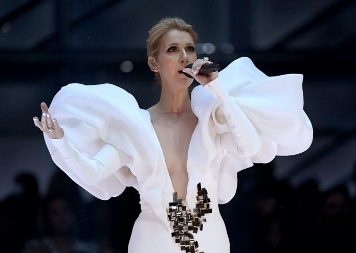 Celine Dion performs at the 2017 Billboard Music Awards.  She wears a white gown with large puffed shoulders and long sleeves and mirror-like embellishments at the waist.  Sony is now working on a Celine Dion biopic with the singer's full backing.