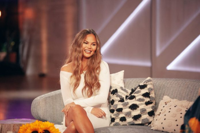 Chrissy Teigen, dressed in a cream dress, smiles while sitting on a couch during an interview.