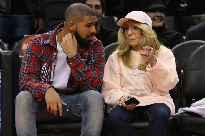 Drake and Sandy Graham in a red and gray plaid shirt and a blush Ovo sweat shirt sit court side at the Toronto Raptors vs Cleveland Cavaliers game.